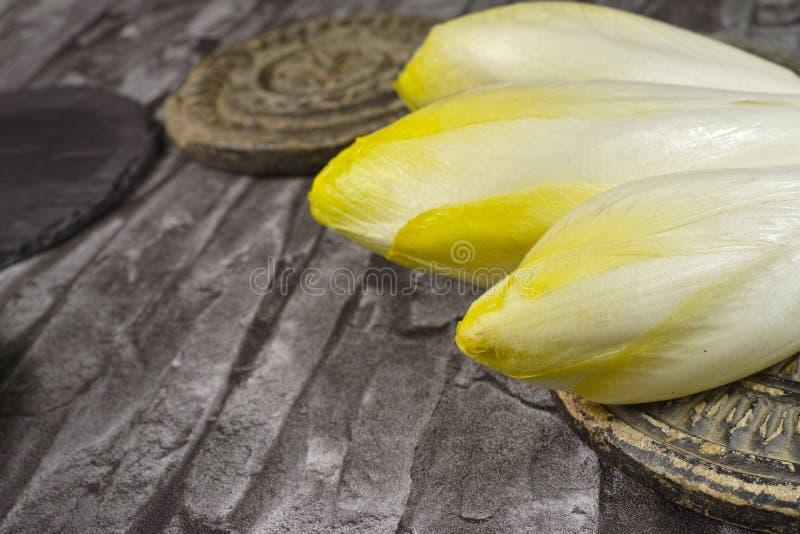 As folhas frescas da salada da chicória colocadas em um cinza apedrejam placas imagem de stock