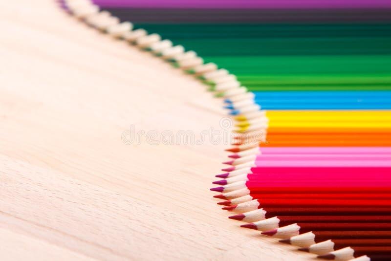 As fontes de escola coloriram os lápis que formam uma onda, em um fundo de madeira foto de stock