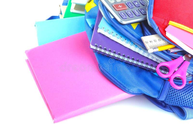 As fontes diferentes dos artigos de papelaria e de escola que encontram-se em uma escola backpack em um fundo isolado branco fotos de stock royalty free