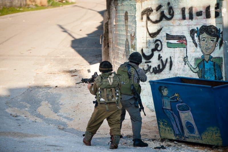 As forças armadas israelitas invadem a vila palestina imagem de stock