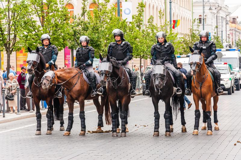 As forças policiais montadas armadas que estão no início da parada de orgulho na rua de Gedimino Comemoração do evento lésbica, a imagem de stock royalty free