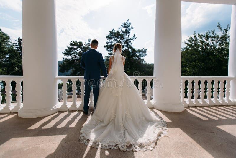 As fotos completos do noivo em um terno azul e da noiva em um trem com um trem estão entre as colunas brancas e imagem de stock