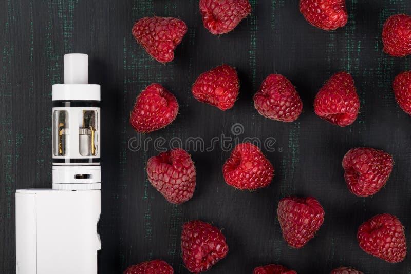 As framboesas vermelhas e o cigarro eletrônico branco encontram-se em um fundo escuro fotos de stock royalty free
