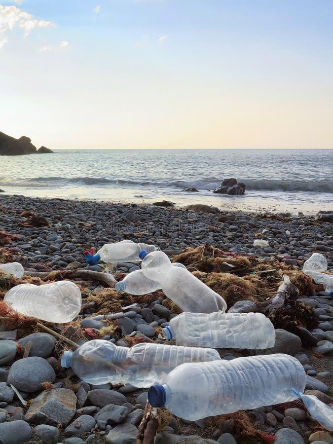As garrafas bebendo do plástico lavaram na linha costeira ou na praia atlântica que poluem o ambiente em spain do norte imagem de stock