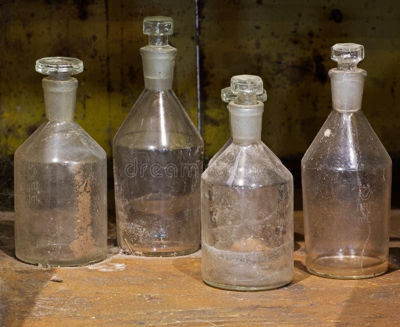 As garrafas de vidro do reagente velho na tabela empoeirada foto de stock