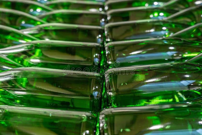 As garrafas de vinho verdes encheram-se com o vinho branco empilhado fotografia de stock