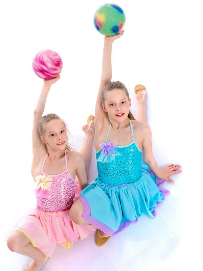 As ginastas das meninas sentam-se no assoalho imagem de stock
