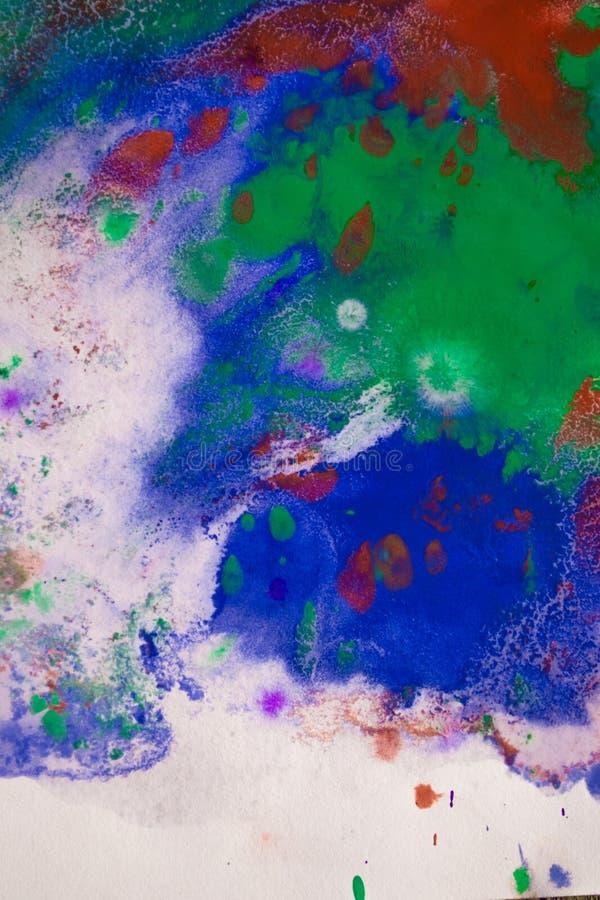 As gotas com as raias da pintura diferente das cores são misturadas e absorvidas fotografia de stock
