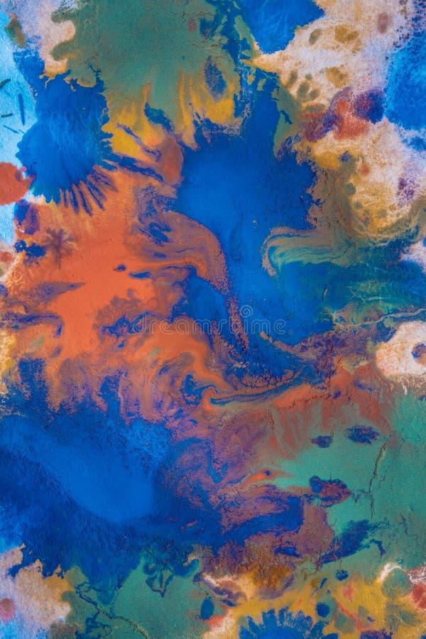 As gotas com as raias da pintura diferente das cores são misturadas e absorvidas imagem de stock