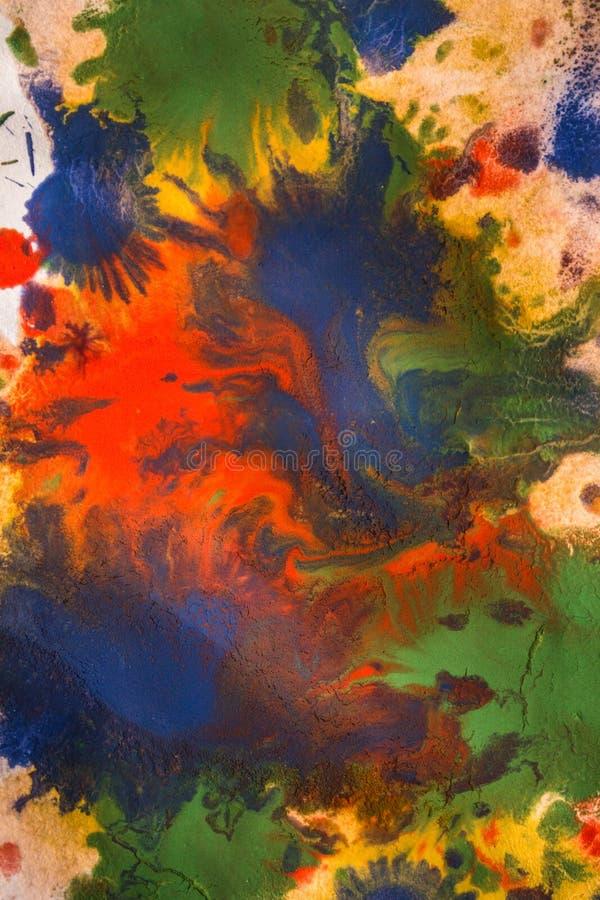 As gotas com as raias da pintura diferente das cores são misturadas e absorvidas fotos de stock