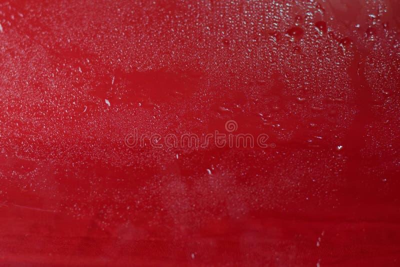 As gotas da ?gua fecham-se acima Fundo vermelho abstrato dos waterdrops, gotas imagem de stock royalty free