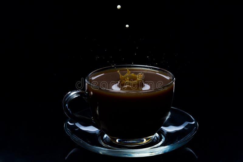 As gotas do leite caem em um copo de vidro com café preto, fundo preto foto de stock