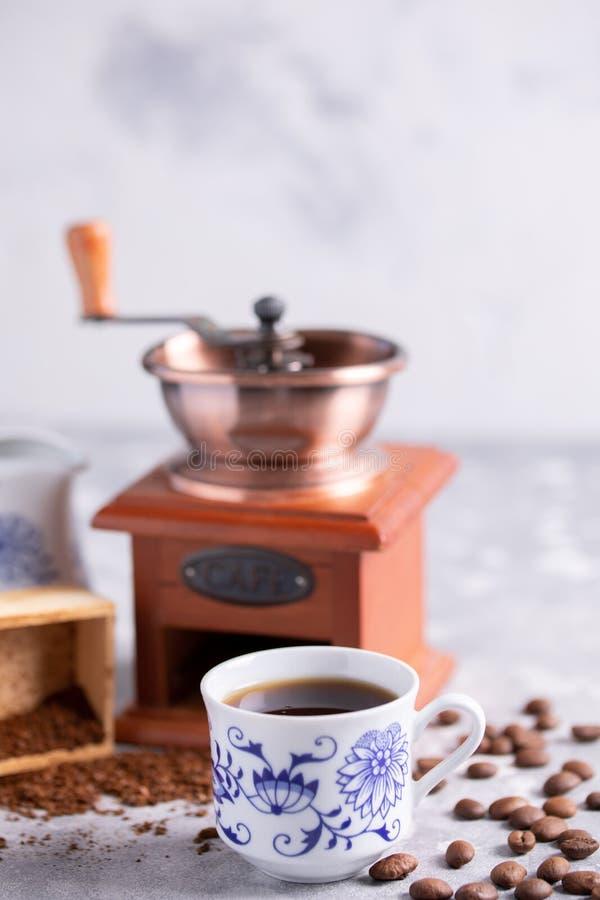 As grões do café caem fora de um moedor de café do vintage Café preto quente em um copo bonito da porcelana na tabela Um cof boni fotos de stock royalty free