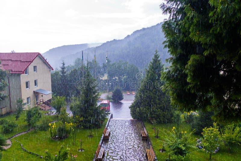 As grandes gotas da chuva caem na casa com um parque pequeno em torno dele foto de stock