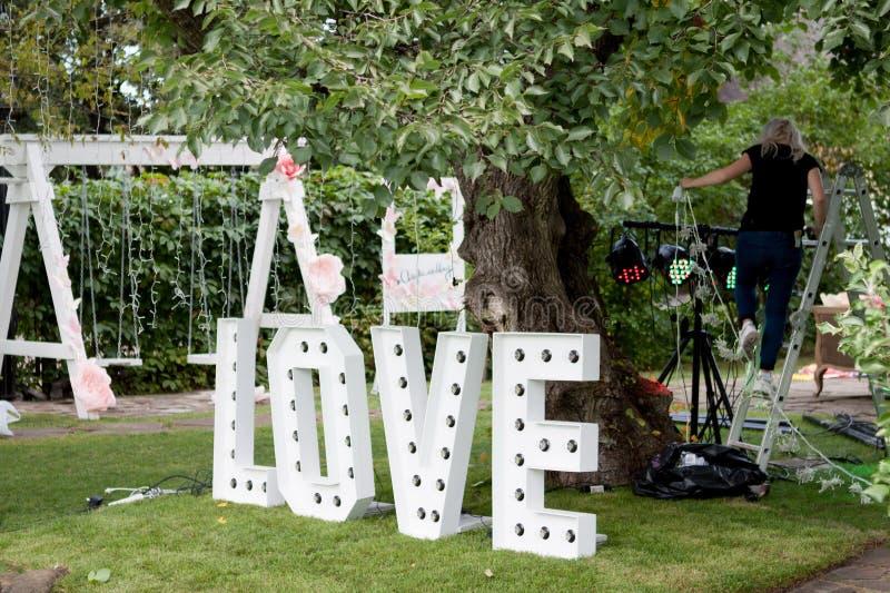 As grandes letras AMAM com bulbos estão em um gramado verde Amor da decoração do casamento fotos de stock royalty free