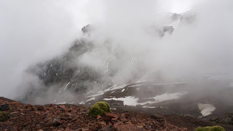 As grandes nuvens nadam através do desfiladeiro ?rea montanhosa A neve é visível nas inclinações de montanha foto de stock royalty free
