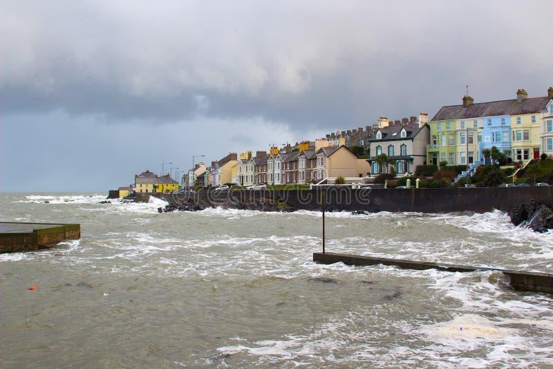 As grandes ondas do Mar da Irlanda durante uma tempestade do inverno golpeiam a parede do porto no furo longo na Irlanda de Bango imagem de stock