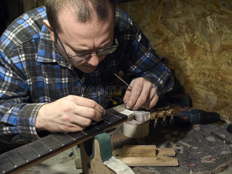 As guitarra Luthiers verificam a precisão do ajuste da porca fotos de stock