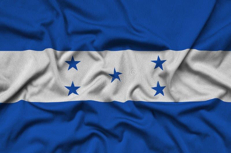 As Honduras embandeiram são descritas em uma tela de pano dos esportes com muitas dobras Bandeira da equipe de esporte imagem de stock