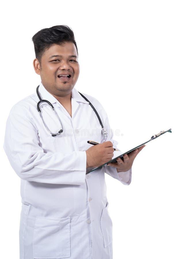 As imagens do doutor sério escrevem um diagnóstico e um olhar na câmera foto de stock