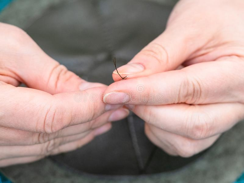 As inserções do artesão rosqueiam na agulha para costurar um malote foto de stock
