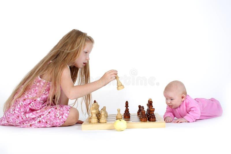 As irmãs 8 anos e bebês de três meses jogam na xadrez foto de stock