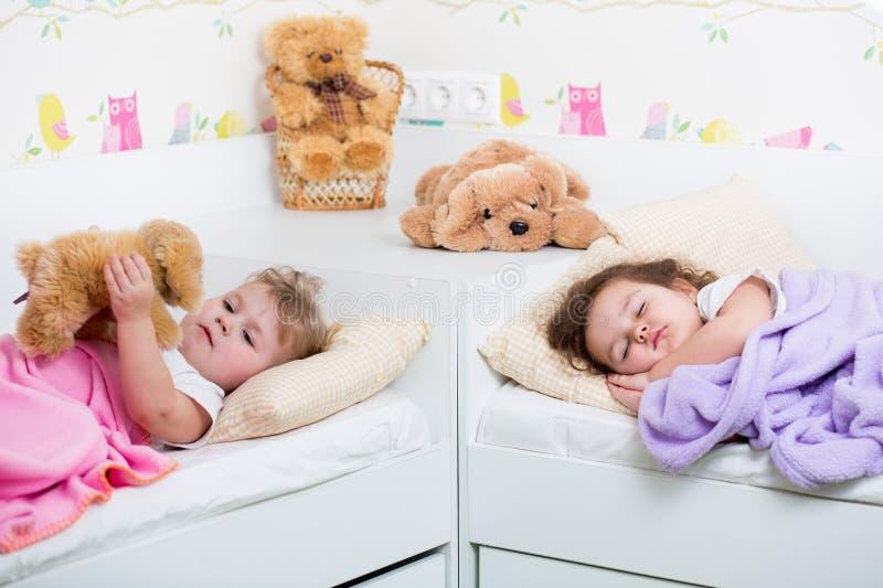 As irmãs das crianças que dormem e acordam imagem de stock