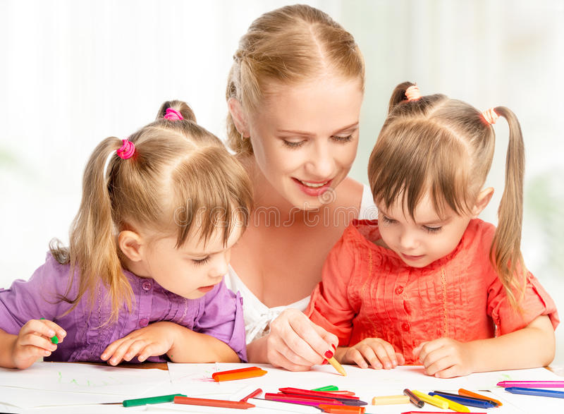 As irmãs gêmeas das crianças tiram pinturas com sua mãe no jardim de infância foto de stock