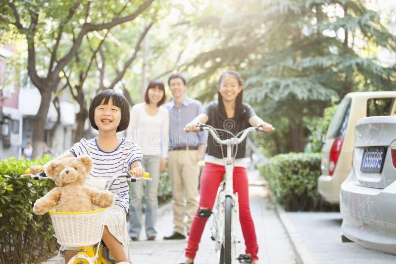 As irmãs montarem suas bicicletas quando relógio dos pais foto de stock