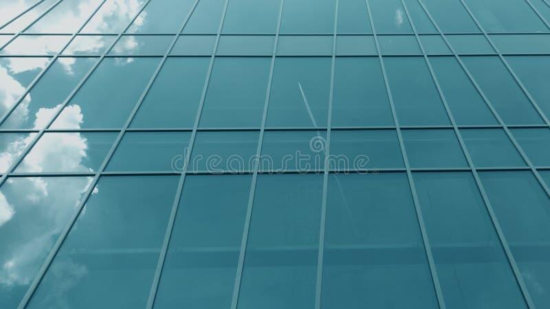 As janelas de vidro modernas da fachada refletem o plano e nuvens de voo fotografia de stock royalty free