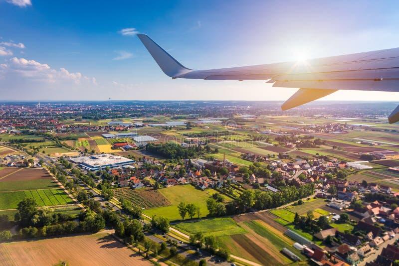 As janelas do avião veem acima da terra no marco para baixo Vista de uma janela do avião sobre uma elevação do voo da asa acima d imagem de stock