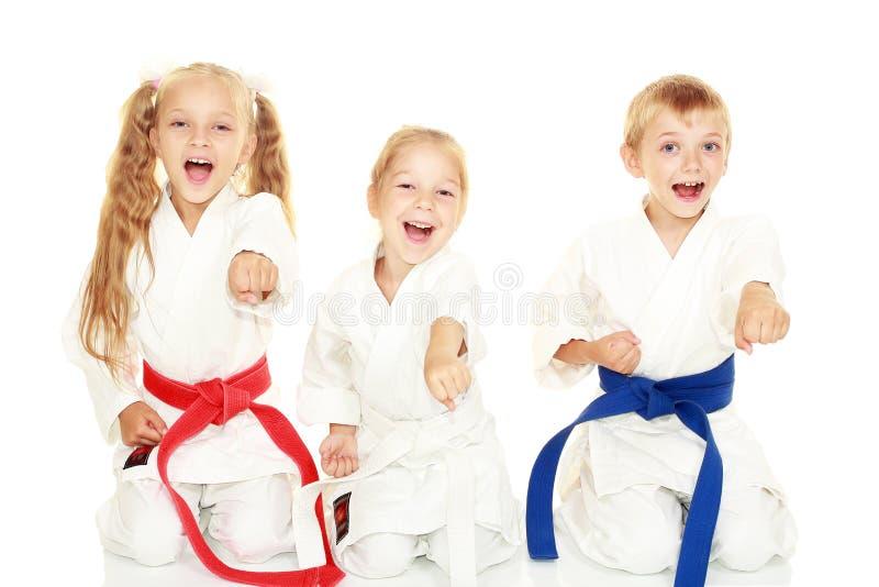 As jovens crianças com um sorriso no quimono que senta-se em um perfurador ritual do karaté da pose armam-se fotografia de stock royalty free