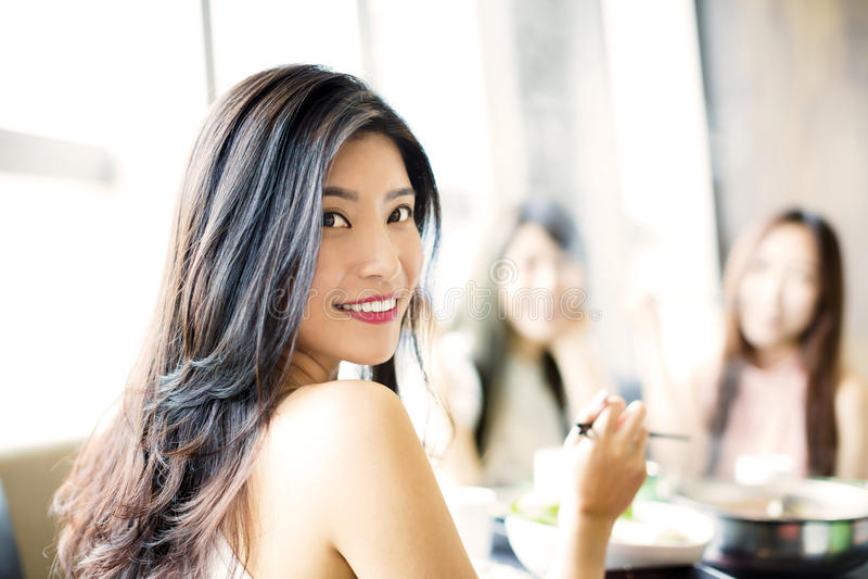 As jovens mulheres agrupam comer o potenciômetro quente foto de stock royalty free