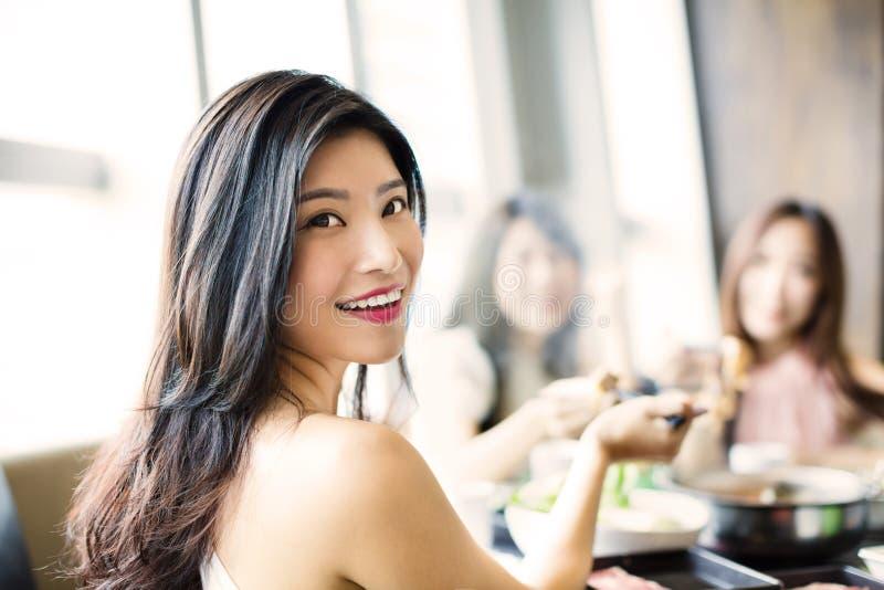 As jovens mulheres agrupam comer o potenciômetro quente imagem de stock