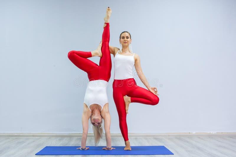 As jovens mulheres bonitas fazem a ioga praticando do grupo de pessoas da ioga no gym foto de stock royalty free