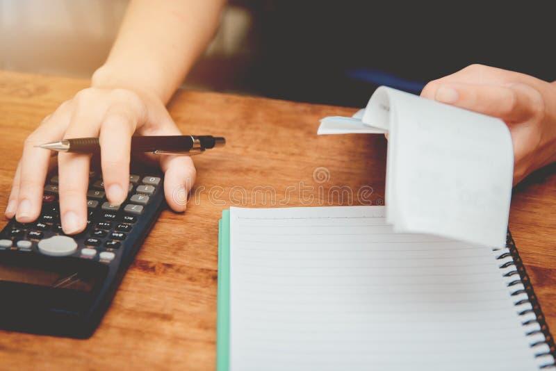 As jovens mulheres da mão estão calculando o imposto de renda individual para enviar a informação às agências governamentais imagem de stock