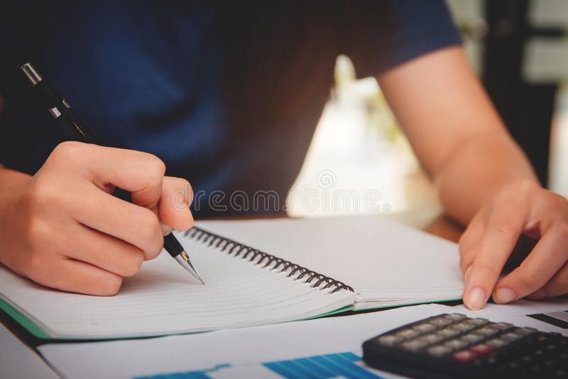 As jovens mulheres da mão estão calculando o imposto de renda individual para enviar a informação às agências governamentais imagens de stock