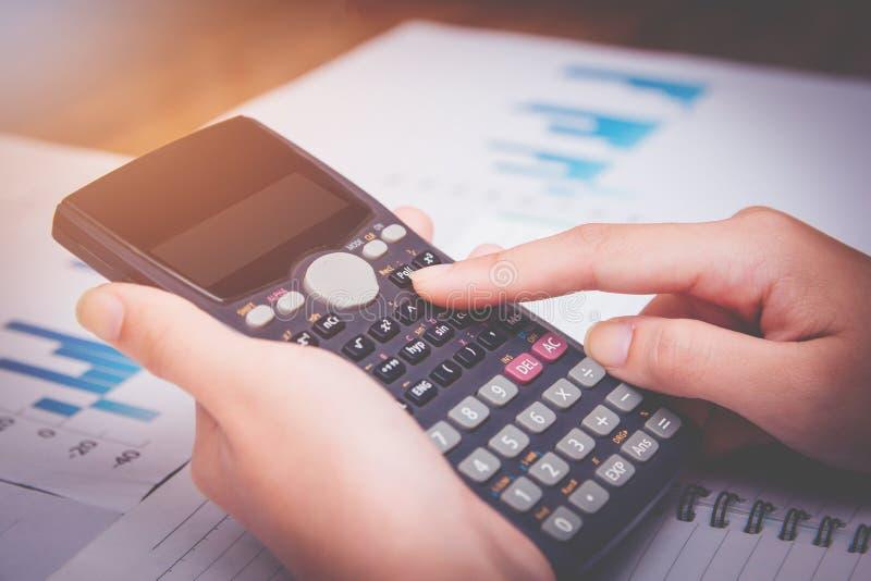 As jovens mulheres da mão estão calculando o imposto de renda individual para enviar a informação às agências governamentais fotos de stock