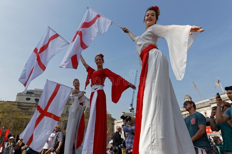 As jovens mulheres em pernas de pau agitam bandeiras inglesas em Trafalgar Square foto de stock royalty free