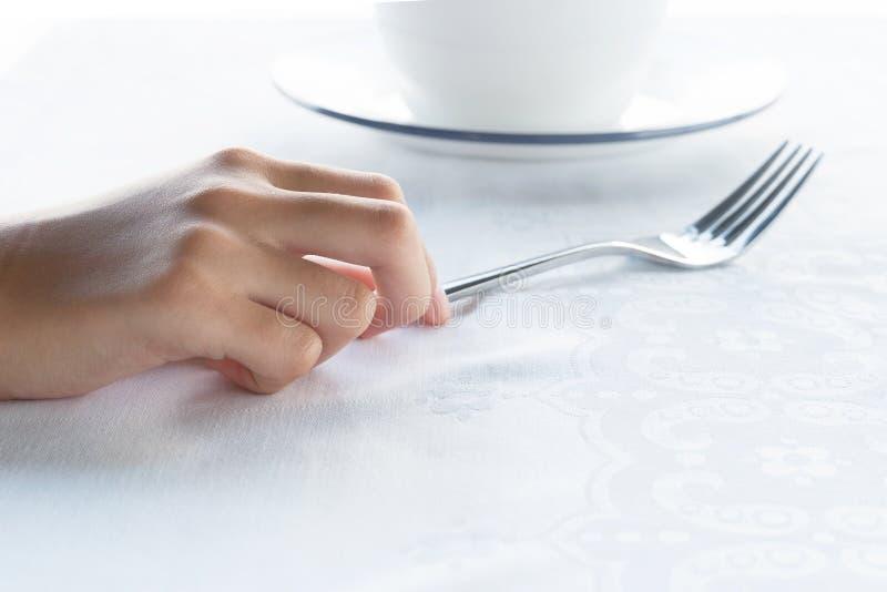 As jovens mulheres entregam guardar a forquilha do metal e o prato branco para o alimento de café da manhã da manhã no fundo bran imagens de stock