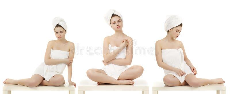As jovens mulheres envolveram a toalha isolada no fundo branco imagens de stock royalty free