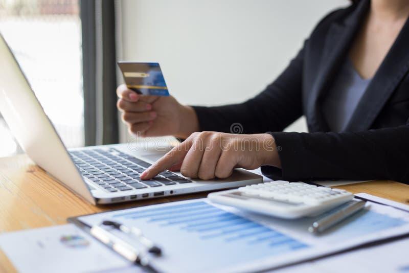 As jovens mulheres estão comprando produtos em linha através do Internet e estão fazendo pagamentos através dos cartões de crédit imagem de stock royalty free