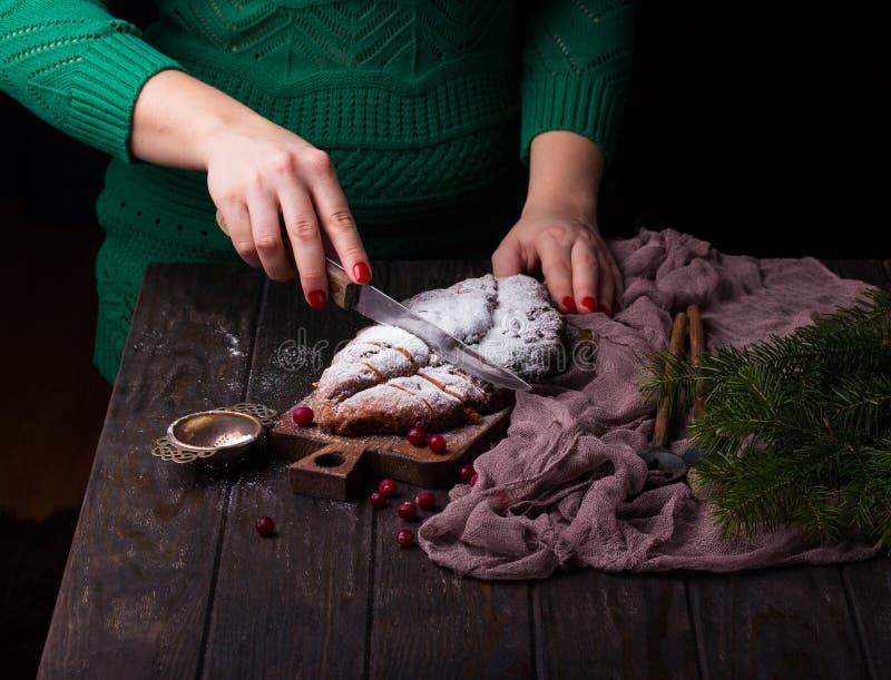 As jovens mulheres estão cozinhando o bolo do Natal Stollen com maçapão, bagas e porcas imagem de stock