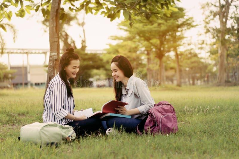 As jovens mulheres estudam junto o livro de leitura foto de stock