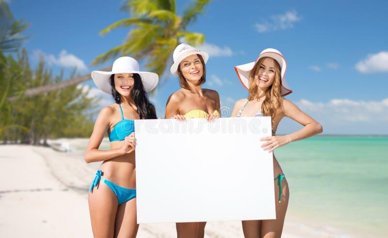 As jovens mulheres felizes com placa branca no verão encalham imagem de stock royalty free
