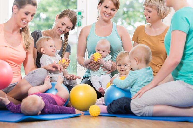 As jovens mulheres na mãe e na criança agrupam o jogo com seu ki do bebê imagens de stock