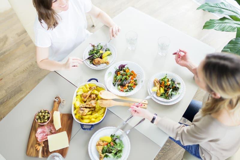 As jovens mulheres que comem o jantar junto na tabela com galinha roasted, batata serviram com salada verde, azeitonas, água foto de stock