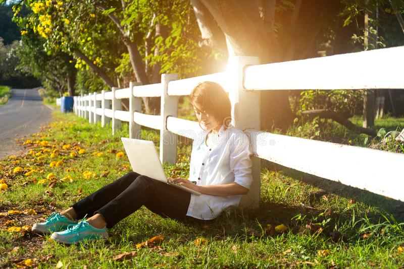 As jovens mulheres que encontram-se no verão gramam o jogo do portátil e relaxam, dia ensolarado, foto de stock royalty free