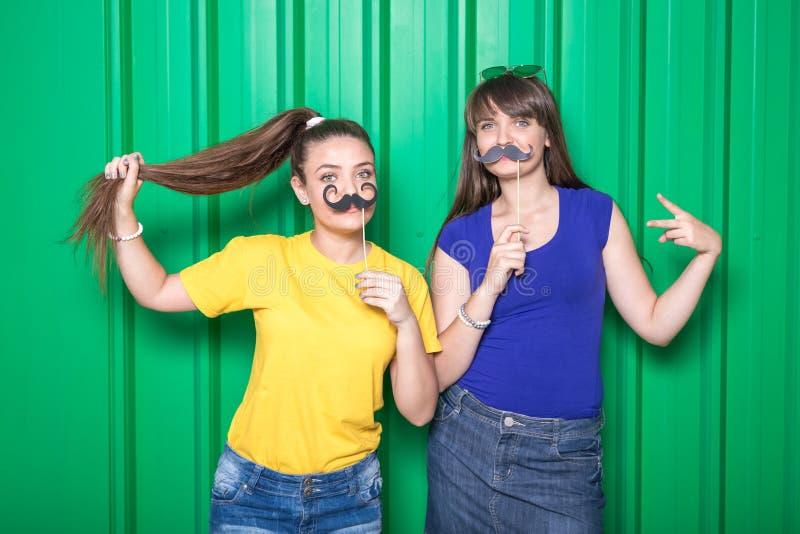 As jovens mulheres que mantêm suportes da bota da foto contra o metal verde muram o fundo Conceito do partido fotografia de stock royalty free