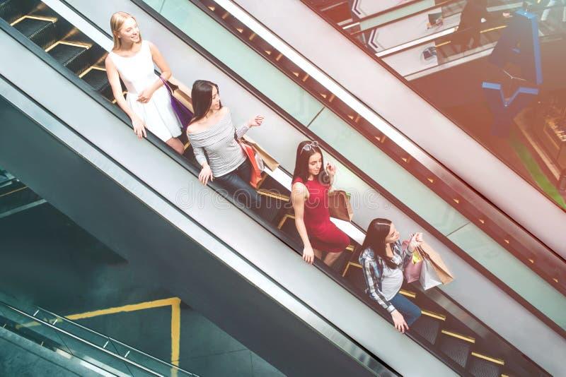 As jovens senhoras estão montando na escada rolante Estão estando um após o outro Cada um deles tem sacos de compras São imagem de stock royalty free